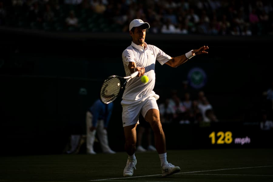Novak Djokovic Wimbledon 2019 in the dusk plays a flying forehand