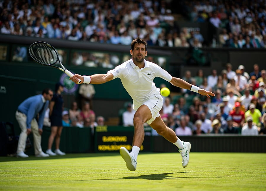 Novak Djokovic reaching at Wimbledon